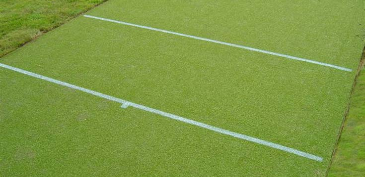 Creases marked on a cricket carpet with a white aerosol spray.