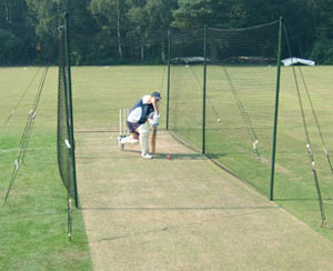 Cricket net supported by wooden poles and guy ropes.